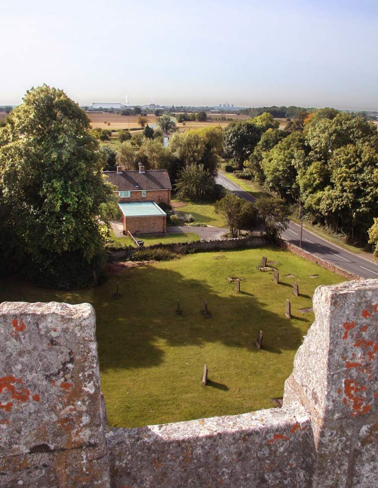 "View from the top of the tower to the South - Ferrybridge power station on the horizon. The Churchyard, often mentioned in the wills of old-time parishioners, is stated in the Terrier of 1809 to be ""fenced by the Vicar or his Tenant, except the North side & part of the ""West side which are maintained by the Parishioners. The East and West Gates are maintained by the Parishioners. The West Stile is upheld by John Middleton of Little Fenton, the South Stile next the Road by David Marshall of Matram Hall. It is bounded on three sides by a stone wall. The West side is bounded by a brick wall, with iron palisading (a fence made of pales driven into the ground) and two iron gates. The repair is undertaken by the Vicar & Churchwardens and the Parochial Church Council. The brick wall and the iron palisading were erected in 1883 and a stone wall on the North side in 1884. A public path runs through the churchyard from the main road to the field at the E. and is continued through the fields, over East Car Drain. In 1912 the North Side of the Churchyard was drained so as to allow a grave of six feet in depth. The drain is carried to the E. Car Drain and there are three man holes at intervals. An Easement fee of two shillings and sixpence per annum is paid to the owner of the property."""