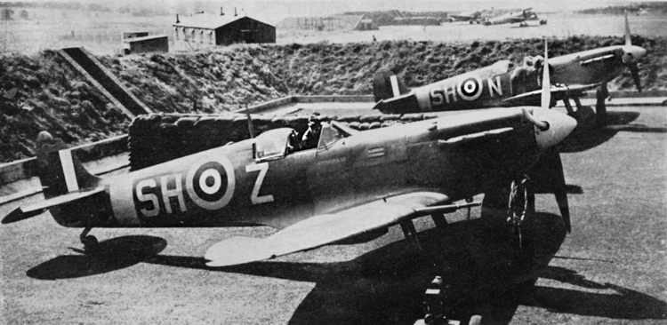 Spitfire VBs of No. 64(F) Squadron. Aircraft in foreground is 'Atchasmickar', a presentation machine. It carries the Squadron Leader's pennant. Note the Tin. Red centre spot of'the 35in. roundel. Fin stripes are the standard 27m. x 24in. The camouflage scheme is probably Mixed Grey (Medium Sea Grey and Night) and Dark Green, with Medium Sea Grey under surfaces.